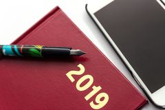 Ciérrese para arriba de 2019 diarys de cuero rojos con la pluma en el fondo blanco fotografía de archivo libre de regalías
