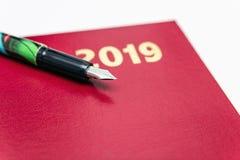 Ciérrese para arriba de 2019 diarys de cuero rojos con la pluma en el fondo blanco fotografía de archivo