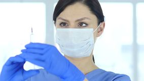 Ciérrese para arriba de doctor en la máscara que celebra la inyección, listo para inyectar almacen de metraje de vídeo