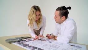 Ciérrese para arriba de dos arquitectos que discuten plan junto en el escritorio con los modelos metrajes
