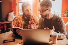 Ciérrese para arriba de dos hombres barbudos que se sientan junto en un pequeño café El individuo a la derecha explaiting algo al Foto de archivo libre de regalías