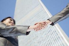 Ciérrese para arriba de dos hombres de negocios que sacuden las manos por el World Trade Center de China en Pekín Foto de archivo libre de regalías