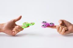 Ciérrese para arriba de dos manos que juegan con los hilanderos de la persona agitada Fotografía de archivo libre de regalías