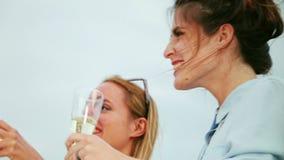 Ciérrese para arriba de dos mujeres jovenes que beben el champán almacen de metraje de vídeo