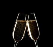 Ciérrese para arriba de dos vidrios de Champán que tintinean juntos aislados en negro Fotografía de archivo