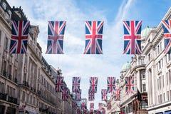 Ciérrese para arriba de edificios en Regent Street London con la fila de banderas británicas para celebrar la boda de príncipe Ha imagenes de archivo