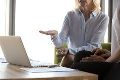 Ci?rrese para arriba de empresarias se inspiran la negociaci?n en oficina fotos de archivo