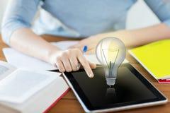 Ciérrese para arriba de estudiante con la bombilla en la PC de la tableta Imágenes de archivo libres de regalías