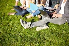 Ciérrese para arriba de estudiantes con el ordenador portátil que se sienta en hierba Imágenes de archivo libres de regalías
