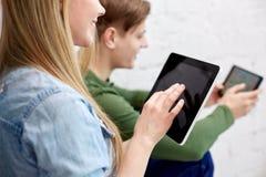 Ciérrese para arriba de estudiantes con PC de la tableta en la escuela Imagenes de archivo