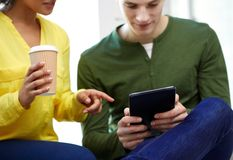 Ciérrese para arriba de estudiantes con PC y café de la tableta Imágenes de archivo libres de regalías