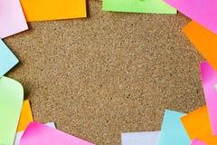 Ciérrese para arriba de etiquetas engomadas del papel en blanco en tablero del corcho Imágenes de archivo libres de regalías