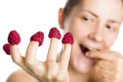 Ciérrese para arriba de frambuesas en los dedos. Foto de archivo libre de regalías