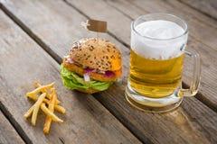 Ciérrese para arriba de fritadas con el vidrio de la hamburguesa y de cerveza Fotografía de archivo