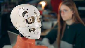 Ciérrese para arriba de gestos faciales de un cyborg con una señora que trabaja en el fondo almacen de metraje de vídeo