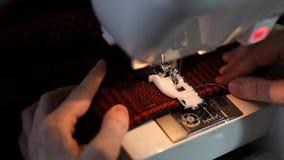 Ciérrese para arriba de hacer la costura decorativa en el paño a cuadros en la máquina de coser con el carril de guía y la lámpar almacen de metraje de vídeo