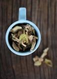 Ciérrese para arriba de hojas de té en taza azul imagenes de archivo
