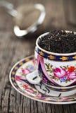 Ciérrese para arriba de hojas de té en taza del vintage foto de archivo