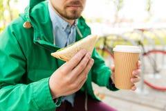 Ciérrese para arriba de hombre con café y el bocadillo en la calle Imagenes de archivo