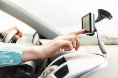 Ciérrese para arriba de hombre con el navegador de los gps que conduce el coche Imagenes de archivo