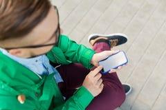 Ciérrese para arriba de hombre con el smartphone que se sienta en banco Foto de archivo libre de regalías
