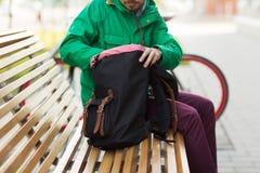 Ciérrese para arriba de hombre con la mochila en banco de la ciudad Fotografía de archivo libre de regalías