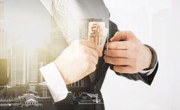 Ciérrese para arriba de hombre de negocios con el dinero euro Imagen de archivo libre de regalías