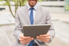 Ciérrese para arriba de hombre de negocios con PC de la tableta en ciudad Imágenes de archivo libres de regalías