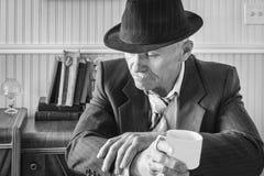 Ciérrese para arriba de hombre de negocios en un traje con la taza de café imagen de archivo