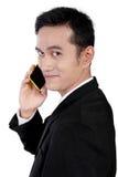 Ciérrese para arriba de hombre de negocios sonriente en el teléfono, aislado en blanco Imagen de archivo libre de regalías
