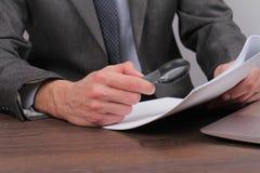 Ciérrese para arriba de hombre de negocios usando la lupa para leer el contrato Lupa y documento Abogado minucioso que comprueba  Imagen de archivo libre de regalías