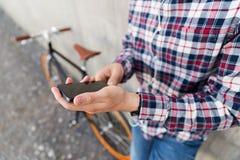 Ciérrese para arriba de hombre del inconformista con smartphone y bike Foto de archivo
