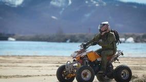 Ciérrese para arriba de hombre en el equipo protector y del casco que conduce su ATV y que se mueve a lo largo de la orilla con l almacen de video