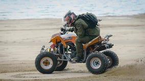 Ciérrese para arriba de hombre en el equipo protector y del casco que deriva en su ATV en la playa con el mar en el fondo almacen de video