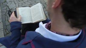 Ciérrese para arriba de hombre en el traje retro que se sienta en banco y lea el libro, visión trasera metrajes