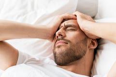 Ciérrese para arriba de hombre en la cama que sufre de dolor de cabeza Imagen de archivo libre de regalías