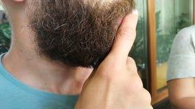 Ciérrese para arriba de hombre habla y piensa frotando ligeramente su barba almacen de video