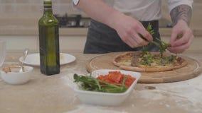 Ciérrese para arriba de hombre irreconocible que las manos ponen arugula en el top de su pizza que miente en la tabla concepto de almacen de video
