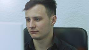 Ciérrese para arriba de hombre joven atractivo usando el ordenador en su lugar de trabajo En fondo verde metrajes