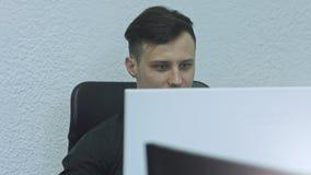 Ciérrese para arriba de hombre joven atractivo usando el ordenador en su lugar de trabajo En fondo verde almacen de video