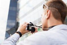 Ciérrese para arriba de hombre joven con la cámara digital en ciudad Foto de archivo
