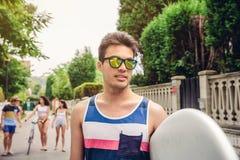 Ciérrese para arriba de hombre joven con las gafas de sol que sostienen la tabla hawaiana Foto de archivo