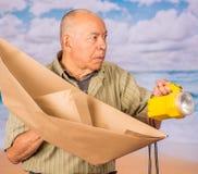 Ciérrese para arriba de hombre maduro con el barco y la linterna amarilla, concepto para las aspiraciones, dirección, estrategia  imagen de archivo