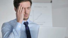 Ciérrese para arriba de hombre de negocios joven con el funcionamiento del dolor de cabeza en oficina almacen de metraje de vídeo