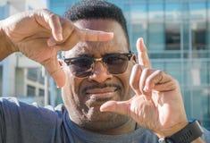 Ciérrese para arriba de hombre negro envejecido middlle con los fingeres que enmarcan la cara imagen de archivo