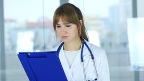 Ciérrese para arriba de informes médicos de lectura del doctor de sexo femenino foto de archivo