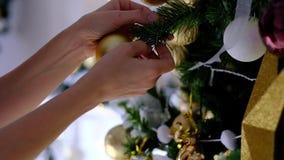 Ciérrese para arriba de juguetes de oro en el árbol de Chrismas y de luz de hadas del centelleo en fondo almacen de video