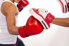 Ciérrese para arriba de la acción del entrenamiento del boxeo en clase de la aptitud en la parte posterior del blanco Fotos de archivo libres de regalías