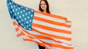 Ciérrese para arriba de la bandera joven de Ginger Woman Holding Up American almacen de metraje de vídeo