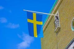 Ciérrese para arriba de la bandera sueca en un edificio Imagenes de archivo